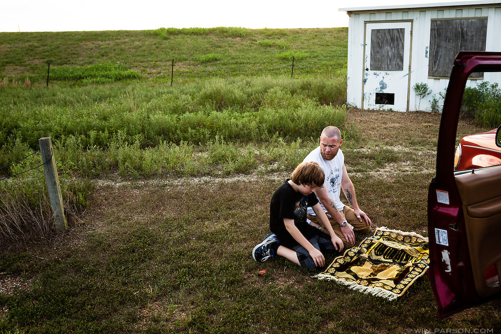 Khalil Holmes, 11, prays with his father Abdul-Hakim Holmes at a shooting range outside Oswego, Kansas on August 27, 2011. Holmes converted to Islam before meeting his wife Misty, and together they have raised Khalil in their faith, homeschooling their only son. Abdul-Hakim, who also goes by his given name Dustin, says some relatives, especially an uncle, had a hard time learning to pronounce his son's name.