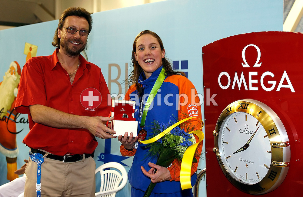 Marleen Veldhuis (R) of the Netherlands wins an Omega watch for the best female performance on day four handed over Omega represent Daniel Kohler (L) at the European Short-Course Swimming Championships at the Maekelaenrinne Swimming Centre in Helsinki, Finland, Sunday December 10, 2006. (Photo by Patrick B. Kraemer / MAGICPBK)