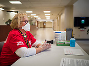 "18 MARCH 2020 - DES MOINES, IOWA: JOLYN CATALDO, a RN with the Polk County Department of Public Health, waits for people to come into the Polk County offices in downtown Des Moines. She screened them before directing them to the proper office. The county reduced its services available to the public in order to reduce the number of people coming into county buildings. County workers are screening people coming into the building, asking about recent travel and health. On Wednesday morning, 18 March, Iowa reported 29 confirmed cases of the Coronavirus. Restaurants, bars, movie theaters, places that draw crowds are closed for at least 30 days. There are no ""shelter in place"" orders in effect anywhere in Iowa but people are being encouraged to practice ""social distancing"" and many businesses are requiring or encouraging employees to telecommute.      PHOTO BY JACK KURTZ"