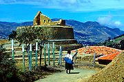 Indigenous woman walks by  the elliptical walls of Ingapirca's Temple of the Sun, Ecuador's most important Inca site.  The temple is a UNESCO World Heritage Trust Site.