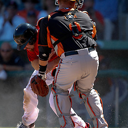 March 7, 2011; Fort Myers, FL, USA; Boston Red Sox third baseman Kevin Youkilis (20) runs into Baltimore Orioles catcher Jake Fox (9) to score during a spring training exhibition game at City of Palms Park.   Mandatory Credit: Derick E. Hingle