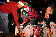 Johny Clark of Englewood (left) and Blake Bradford of Huber Heights add to the collection of toys at the Dublin Pub, the first stop of the Santa Pub Crawl through the Historic Oregon District near downtown Dayton, Saturday, December 10, 2011.  The toys or $10 are admission for the crawl, and get picked up by Marines for the U.S. Marine Corps Toys for Tots program.