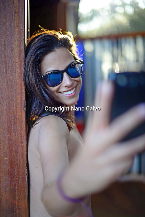 Attractive young woman taking a selfie on the beach, Ibiza, Balearic Islands, Spain