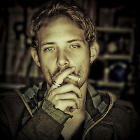 Young man in 20's smoking a cigarette looking into camera