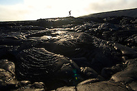 A man walking on the coastal plain old lava flows as VOG from an active volcanic hotspot drifts by in the distance (Volcanic Smag /Fog) Hawaii Volcanoes National Park, Hawaii, USA