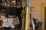 A woman minds a shop in Altar, Sonora, Mexico where migrants wait at the plaza to be transported to the U.S. and Mexico border at Arizona, where they enter the United States illegally.  The shop sells backpacks, caps, dark clothing, and other items used by the crossers.