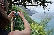 Woman taking pictures of the Na Pali Coast from the Kalalau Trial, Kauai, Hawaii