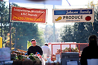 Farmer sorts through tomatoes at the North Carolina State Farmers' Market on a fall day.