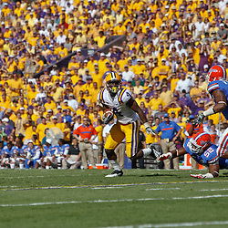 October 8, 2011; Baton Rouge, LA, USA;  LSU Tigers running back Alfred Blue (4) runs past Florida Gators linebacker Jonathan Bostic (52) and Florida Gators defensive end William Green (96) during the first quarter at Tiger Stadium.  Mandatory Credit: Derick E. Hingle-US PRESSWIRE / © Derick E. Hingle 2011