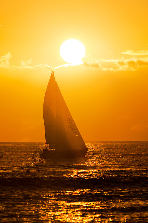 A sailboat sails into the setting sun in Waikiki, Hawaii