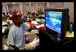28th August, 2005. Hurricane Katrina hits New Orleans, Louisiana. A man watches the approaching storm in sleeping quarters with thousands of people taking shelter in the Hyatt, New Orleans on the eve of the storm.