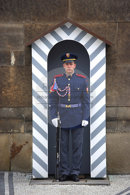 An honor guard stands in a striped pill box at the entry to Prague Castle which is the seat of government in Prague, Czech Republic.