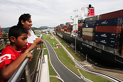 "A mother and son watch a ship pass through the Miraflores Lock in the Panama Canal.  Panama is poised to become the ""next Costa Rica"", though tourists have yet to begin flocking to the central american country.  The Capital, Panama City, is home to the Panama Canal and, due to the former US military presence, is one of the continents capitals most comfortable for people from the United States.  The country offers a variety of eco-tourism opportunities as well as a capital that mixes a modern feel with a colonial center."