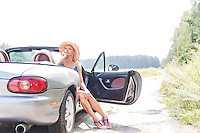 Thoughtful woman sitting in convertible on country road against clear sky