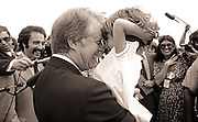 A charmed White House press corps looks on<br /> as President Carter rubs noses with a child.