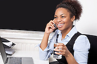 Happy businesswoman using cell phone in front of laptop at desk in office