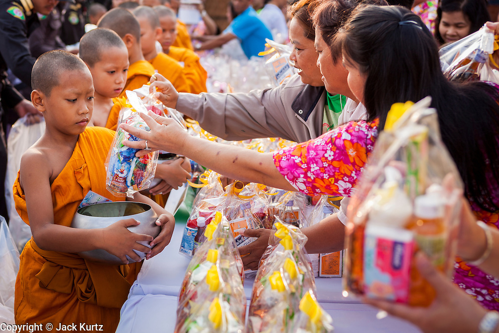 13 APRIL 2014 - BANGKOK, THAILAND:  People give alms to novices (young monks) during a merit making ceremony for Songkran at Bangkok City Hall. Many people go to temples and religious ceremonies to make merit on Songkran. Songkran is celebrated in Thailand as the traditional New Year's Day from 13 to 16 April. Songkran is in the hottest time of the year in Thailand, at the end of the dry season and provides an excuse for people to cool off in friendly water fights that take place throughout the country. Songkran has been a national holiday since 1940, when Thailand moved the first day of the year to January 1.   PHOTO BY JACK KURTZ