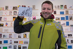 © licensed to London News Pictures. London, UK 23/03/2013. Ian Zanardelli buys a postcard sized artwork made by Zaha Hadid from the Royal College of Art's Secret Postcard Sale. 2,700 postcard sized works of art, which have been donated by artists, designers, illustrators and film-makers including Paula Rego, Julian Opie and David Bailey, sold for £45 at the Royal College of Art in Battersea on Saturday 23 March 2013. Photo credit: Tolga Akmen/LNP