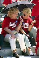 Pearl Gieda, left, 73, of Levittown, Pa., and Mandi Koch, right, 74, of Langhorne, Pa., shield themselves from the sun with an umbrella before AARP members rallied on the front steps of the State Capitol in Harrisburg, Pa., April 16, 2002, seeking the expansion of the PACE drug prescription program. About 1,000 AARP members participated in the rally. (Photo by William Thomas Cain/Getty Images)