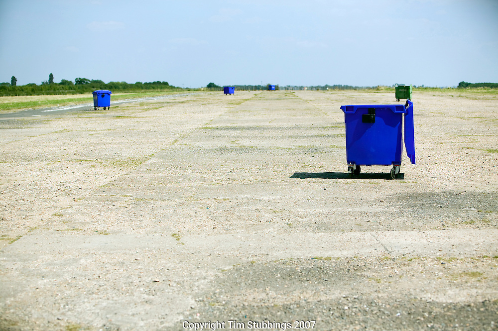Blue large wheeled bins on  level concrete in the sun