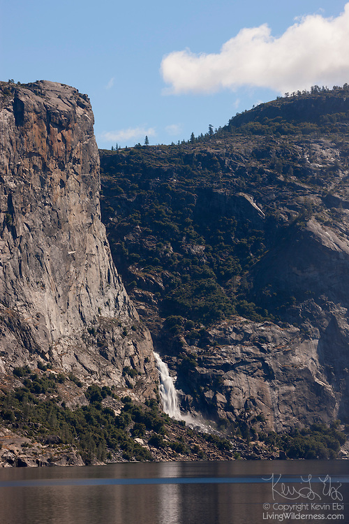 A lower tier of Wapama Falls is reflected in the Hetch Hetchy Reservoir in Yosemite National Park, California. Wapama Falls drops 1,080 feet (330 meters) in three tiers; only the lowest tier is visible here.