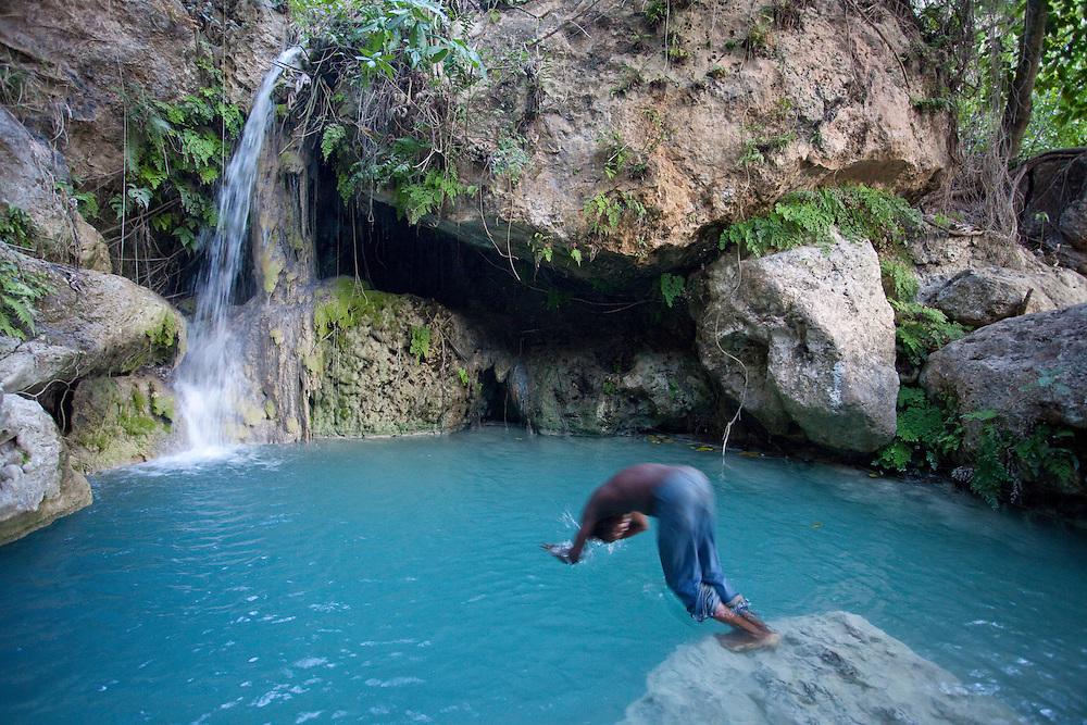 A boy dives into a pool near a spring providing a rare source of fresh water in Ile de La Gonave, Haiti
