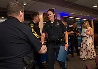 Captain Allan Graton shakes Master Patrol Officer Michelle Cardinal's hand as she and Officer Kira Goodheart receive distinguished unit action awards during the Laconia Police Department's awards dinner Tuesday evening at the Beane Conference Center.  (Karen Bobotas/for the Laconia Daily Sun)