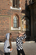 Young visitors walk past the brick architecture of the Church of St Mary on Rynek Glowny market square, on 22nd September 2019, in Krakow, Malopolska, Poland.