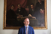 "FLORENCE, ITALY - 29 JUNE 2016: The new director of the Uffizi Gallery Eike Schmidt poses for a portait by the painting ""Four Officers of the Soprintendenza"", by  Mario Cini di Pianzano, in his office at the Uffizi Gallery in Florence, Italy, on June 29th 2016.<br /> <br /> Art historian Eike Schmidt, former curator and head of the Department of Sculpture, Applied Art and Textiles at the Minneapolis Institute of Arts, became the first non-Italian director of the Uffizi in August 2015, replacing Antonio Natali who directed the gallery for 9 years. One of the main goals of the new director is to open the Vasari Corridor to the general public. Currently the corridor can only be visited with group reservations made by external tour and travel agencies throughout the year.<br /> <br /> The Vasari Corridor is is a 1-kilometer-long (more than half mile) elevated enclosed passageway which connects the Palazzo Vecchio with the Palazzo Pitti, passing through the Uffizi Gallery and crossing the Ponte Vecchio above the Arno River, in Florence. The passageway was designed and built in 1564 by Giorgio Vasari in only 6 months to allow Cosimo de' Medici and other Florentine elite to walk safely through the city, from the seat of power in Palazzo Vecchio to their private residence, Palazzo Pitti. The passageway contains over 1000 paintings, dating from the 17th and 18th centuries, including the largest and very important collection of self-portraits by some of the most famous masters of painting from the 16th to the 20th century, including Filippo Lippi, Rembrandt, Velazquez, Delacroix and Ensor."