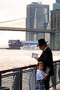 An Jewish man prays with his daughter not far from the smoking remnants of lower Manhattan days after the 9/11. Still many Jews gathered with others along the Hudson on the first day of Rosh Hashanah to recite Tashlikh and pray, to cast ones sins into the water, as their religion dictates.