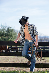 cowboy with open shirt on a ranch