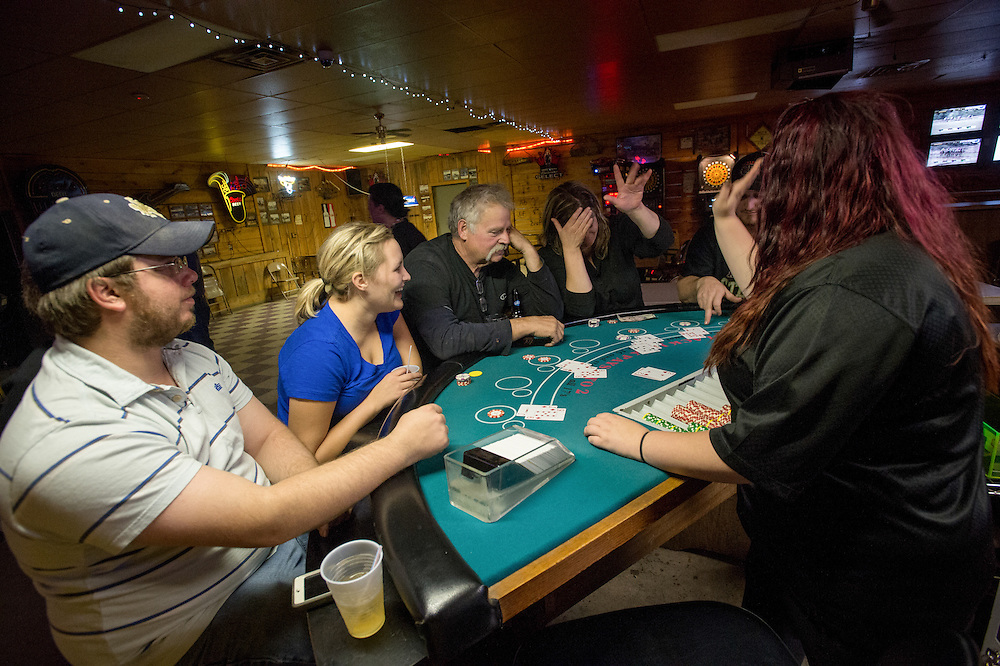 Dusti Page, center right, reacts happily during a small game of Blackjack with her co -workers (L-R Nate Ingalls, Kayla Brim wife of co-worker, and Brent Simmons) from Vision Oil Tools at Champs bar in Williston, N.D., Oct 21, 2013. The amount of jobs the oil boom has provided North Dakota has helped give it the lowest unemployment rate in the United States and and gave it a billion dollar surplus. Shale gas reserves has given the United States more independence over other nations such as Venezuela and countries in the Middle East.