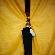 The Ringmaster watches inside the tent from behind curtains at the Cole Brother Circus in Wilmington, North Carolina.