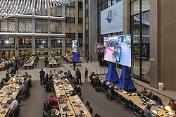 During the first day of an EU Summit, journalists monitor news and activities on giant TV screens, that are set up in the atrium of the European Council headquarters building, which serves as the main press room during summits, on Thursday, Dec. 13, 2012, in Brussels, Belgium. (Photo © Jock Fistick)