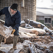 A father and son cut firewood together during the Winter months in Michigan