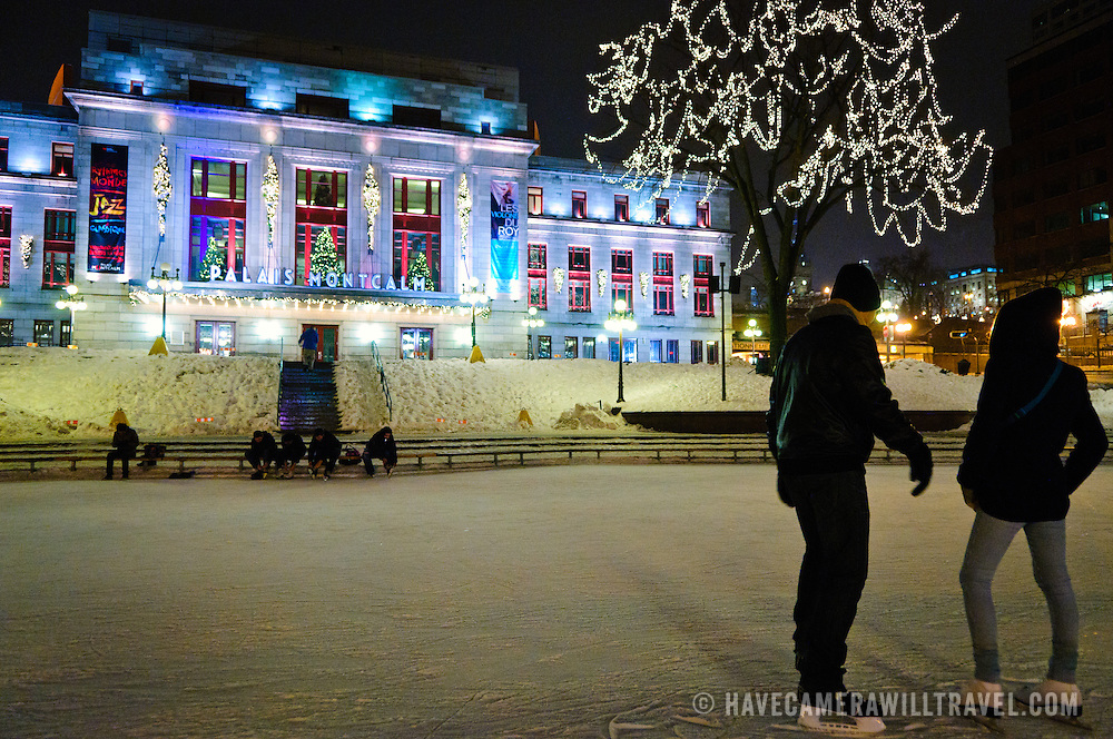 A young couple at an Ice skating rink in front of the Palais Montcalm in Quebec City's Old Town at night in winter.