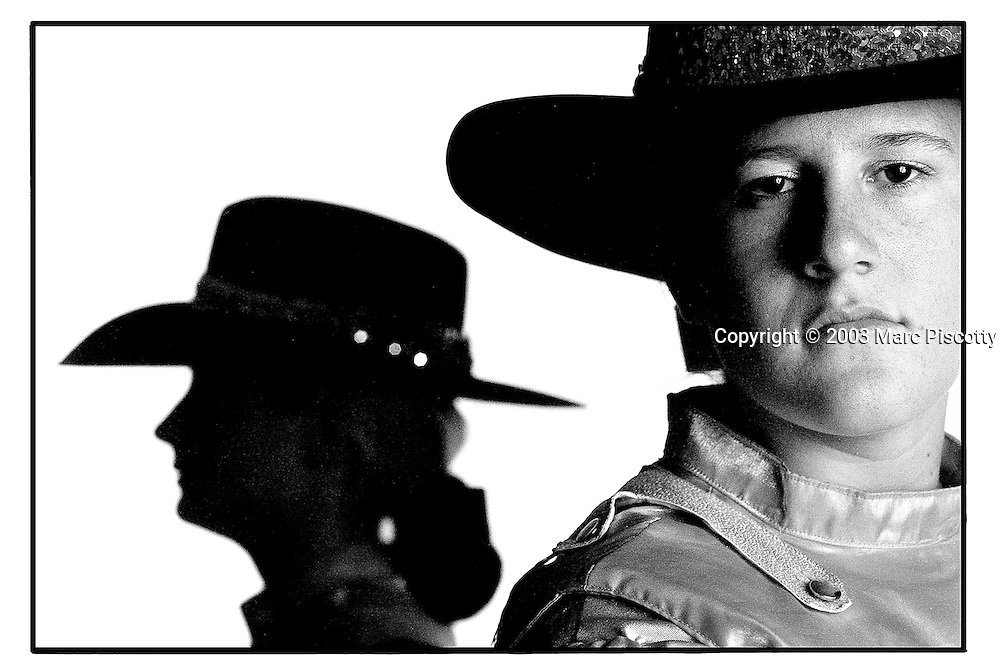 "SHOT 1/23/2003 - Westernaires majors Nikki Simpson (right), 19, and Chelsea Alexander (left, background), 18, are two of the senior leaders in the non-profit youth group that ""encourages leadership, responsibility and self-respect through horsemanship and family participation"". The Westernaires are made up of about 1,000 Jefferson County youths from nine to 19 years old and the group has been performing at the National Western Rodeo for 50 years now. This year's National Western Rodeo is the end of the line performance for both Simpson and Alexander. They've both been in the organization for 10 years and Alexander said of the experience, ""I loved it, they're irreplaceable memories"". Both girls are from Littleton, Co. The National Western Stock Show is held every January at the National Western Complex in Denver, Colorado. First held in 1906, it is the world's largest stock show by number of animals and offers the world?s only carload and pen cattle show in the historic Denver Union Stockyards. The stock show is governed by the Western Stock Show Association, a Colorado 501 (c) 3 institution, which produces the annual National Western Stock Show in an effort to forward the association's mission: ""To preserve the western lifestyle by providing a showcase for the agricultural industry through emphasis on education, genetic development, innovative technology and offering the world's largest agricultural marketing opportunities."" Proceeds from the National Western Stock Show go to the National Western Scholarship Trust. The Trust awards 64 scholarships annually to students studying agriculture and medicine to practice in rural areas at colleges and universities in Colorado and Wyoming..(Photo by Marc Piscotty / © 2003)"