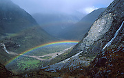 A rainbow shines near a waterfall in Huascaran National Park, Cordillera Blanca, Andes Mountains, Peru, South America. UNESCO honored Huascaran National Park on the World Heritage List in 1985. Cordillera Blanca mountain range is in the Sierra Central of the Peruvian Andes.