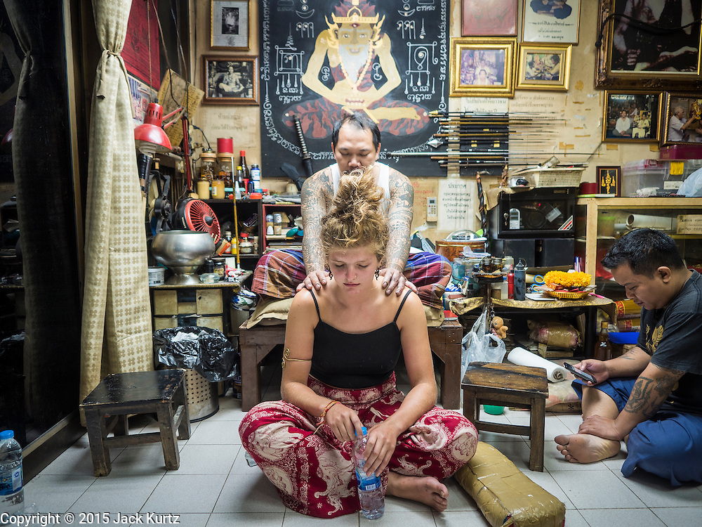 "27 MAY 2015 - BANGKOK, THAILAND: AJARN NENG ONNUT, blesses a sacred Sak Yant tattoo he just gave EMILY, a visitor to Thailand from the United Kingdom. Sak Yant (Thai for ""tattoos of mystical drawings"" sak=tattoo, yantra=mystical drawing) tattoos are popular throughout Thailand, Cambodia, Laos and Myanmar. The tattoos are believed to impart magical powers to the people who have them. People get the tattoos to address specific needs. For example, a business person would get a tattoo to make his business successful, and a soldier would get a tattoo to help him in battle. The tattoos are blessed by monks or people who have magical powers. Ajarn Neng, a revered tattoo master in Bangkok, uses stainless steel needles to tattoo, other tattoo masters use bamboo needles. The tattoos are growing in popularity with tourists, but Thai religious leaders try to discourage tattoo masters from giving tourists tattoos for ornamental reasons.     PHOTO BY JACK KURTZ"