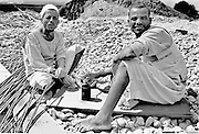 Two construction laborers take tea while seated on a rock pile.  The tea is in a tin can.  Both are barefoot, wearing ragged galabeyyas.