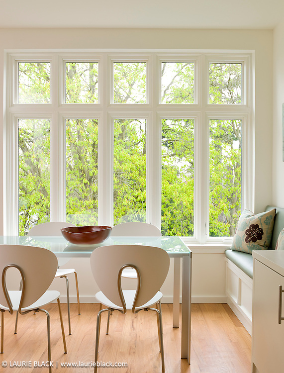 Contemporary white dining room with large window view of trees.