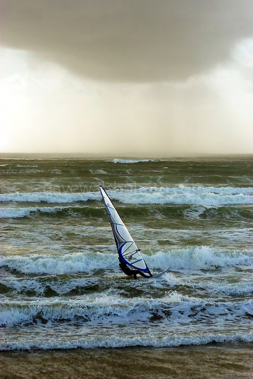 Windsurfer braving the waves at Lahinch Beach, Co. Clare, Ireland.