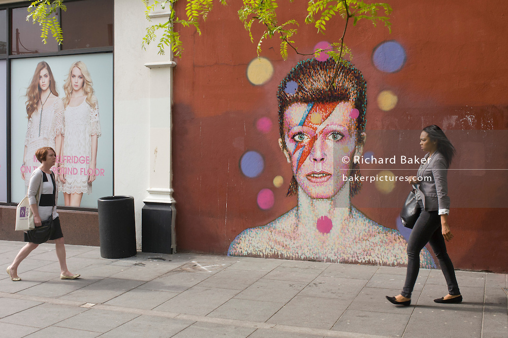 Women walk past the new mural of iconic musician and singer David Bowie has appeared on the wall of Morleys department store in Brixton, Lambeth, south London. The Bowie face is sourced (by artist James Cochran, aka Jimmy C) from the cover of his 1973 album Aladdin Sane at the height of his 1970s fame. The pop icon lived at 40 Stansfield Road, Brixton, from his birth in 1947 until 1953. This cover appeared in Rolling Stone's list of the 500 greatest albums of all time, making #277.