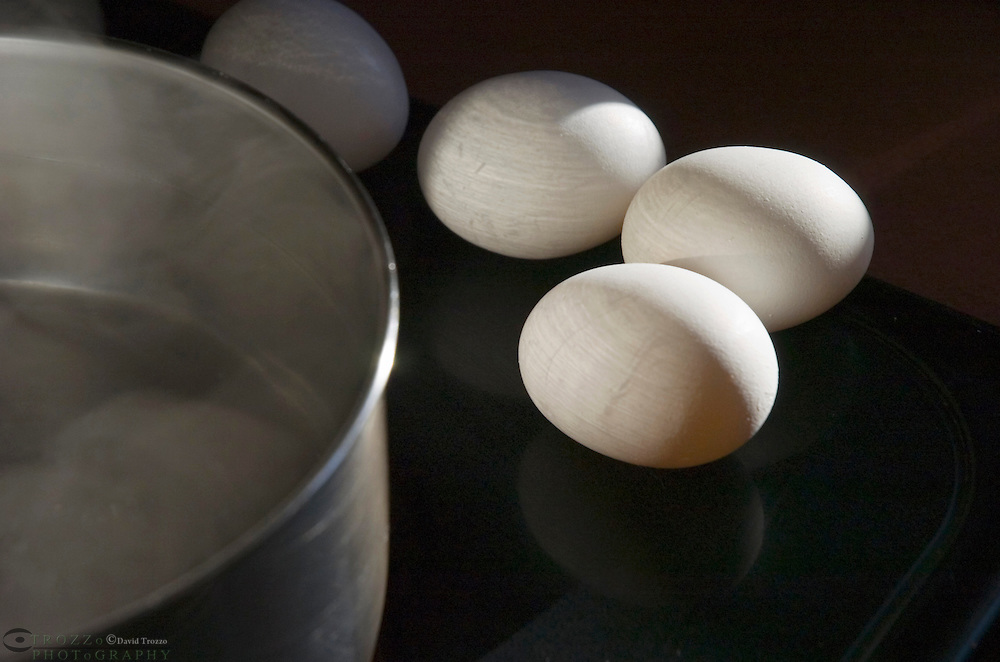 chicken eggs on the kitchen stove with pot of steaming water