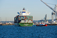 A tug boat pulls a container ship out into Elliott Bay at the Port of Seattle, Seattle, WA USA.