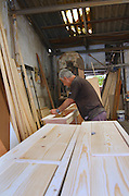 Israel, Tel Aviv, Carpenter at work in an old style workshop filling in imperfections in the surface of the white pine wood