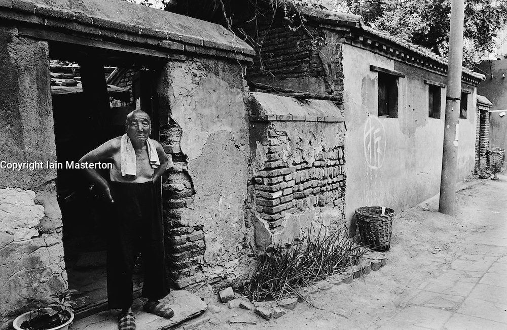 Man standing at door of his old house in a Beijing hutong in  China