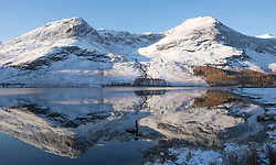 © Licensed to London News Pictures. 07/02/2018. BUTTERMERE, UK. Snow covered fells are reflected in the waters of Buttermere in the Lake District.  Photo credit: Anna Gowthorpe/LNP