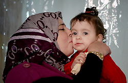 Syrian refugee Ibtissam Bathish Mtaweh, 43, with two-year old Amar, one of her four children, in the basement of a former ski chalet block where they live in Mount Lebanon, just north of the Lebanese capital, after the family fled Syria five years ago.
