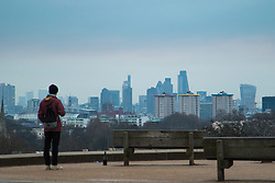Primrose Hill, London, February 15th 2015. A walker takes in the view of London's skyline on a chilly early morning on Primrose Hill, overlooking London&rsquo;s skyline.<br /> ///FOR LICENCING CONTACT: paul@pauldaveycreative.co.uk TEL:+44 (0) 7966 016 296 or +44 (0) 20 8969 6875. &copy;2015 Paul R Davey. All rights reserved.